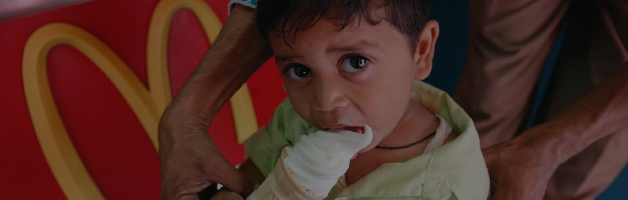 A Child eating ice cream at a McDonalds outlet, India. (Photo by: Salman Quraishi/IndiaPictures/Univ...