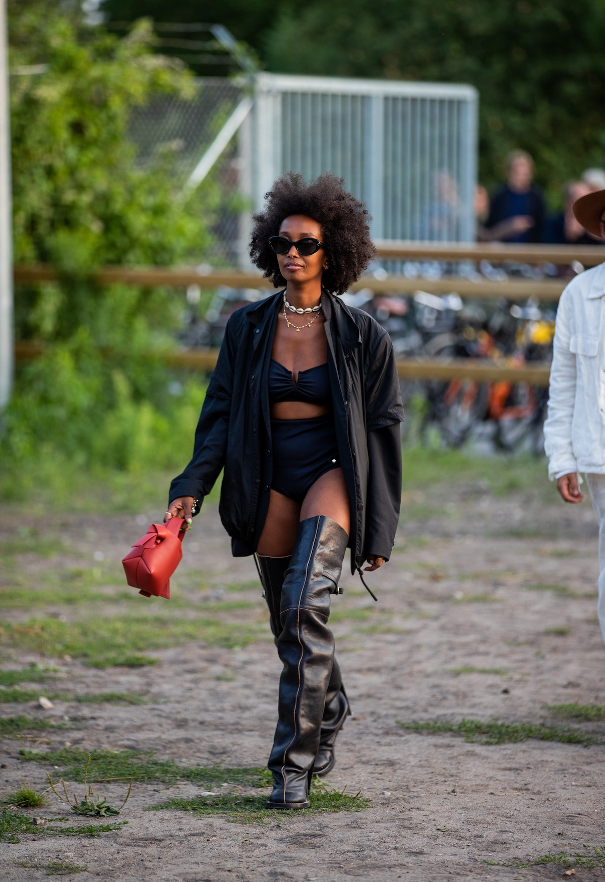 A young fashionable Black woman demonstrates how to wear over-the-knee boots at an event