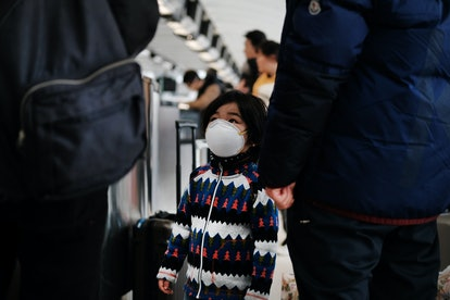 NEW YORK, NEW YORK - JANUARY 31: At the terminal that serves planes bound for China, a child wears a...