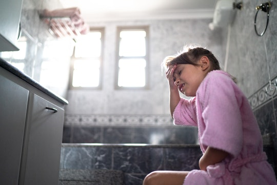 Girl with stomachache using the toilet at home