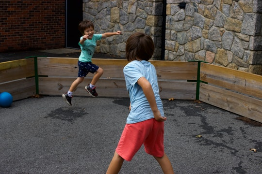 Action shot of two young boys playing with a ball in a gaga pit in the schoolyard.