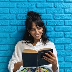 A reader in a crisp white shirt smiles at an open book.