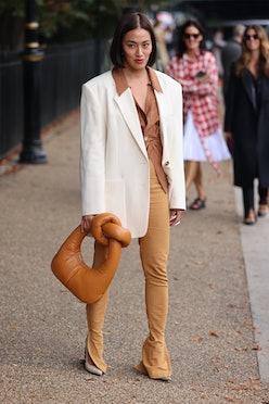LONDON, ENGLAND - SEPTEMBER 20: Guest wearing white jacket, pretzel bag attends ROKSANDA at the Serp...