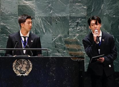 NEW YORK, NEW YORK - SEPTEMBER 20: RM listens as Jungkook of the South Korean boy band BTS speaks at...