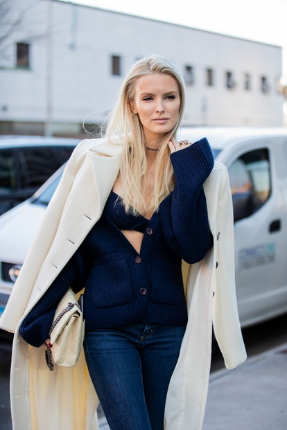 A bralette and cardigan sweater set by Khaite, with jeans and a tailored ivory coat.