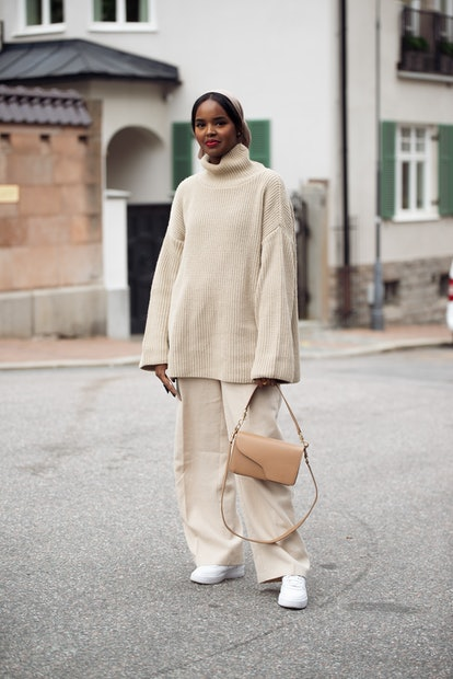 A monochromatic sweater outfit in beige, with sneakers and a bag.