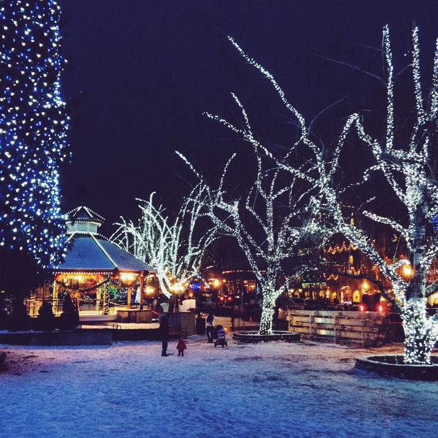 The town of Leavenworth, Washington sits at twilight on a snowy, winter night lit by Christmas light...