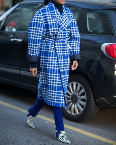 Stirrup leggings with a checkered coat and heeled boots.