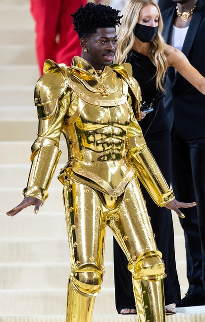 Lil Nas X attends The 2021 Met Gala while wearing gold-plated armor designed by Versace.