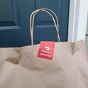 Close-up of the top of a brown paper bag, with handles and a red and white DoorDash safety seal stic...