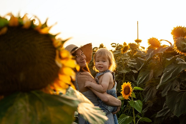 baby and mom in sunflower field