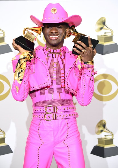 Lil Nas X poses at the 62nd Annual GRAMMY Awards wearing a pink, leather cowboy look.