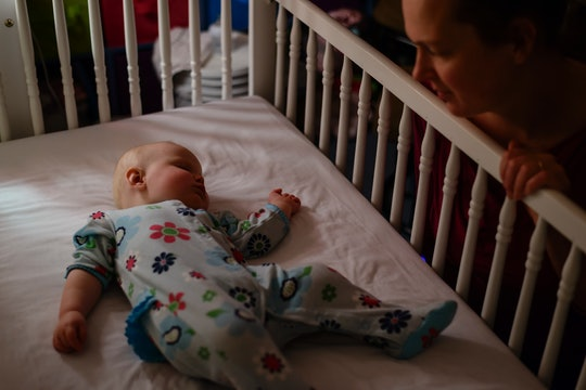 baby sleeping in crib, mom looking at baby
