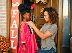 A mother prepares a child's costume before going out trick or treating on Halloween.