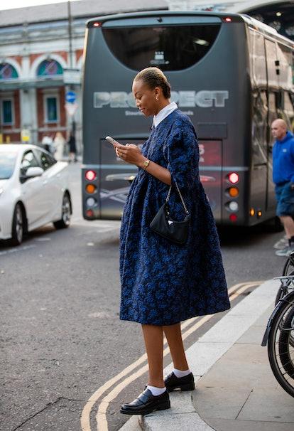 LONDON, ENGLAND - SEPTEMBER 20: A guest is seen wearing navy dress, Prada bag outside Simone Rocha d...