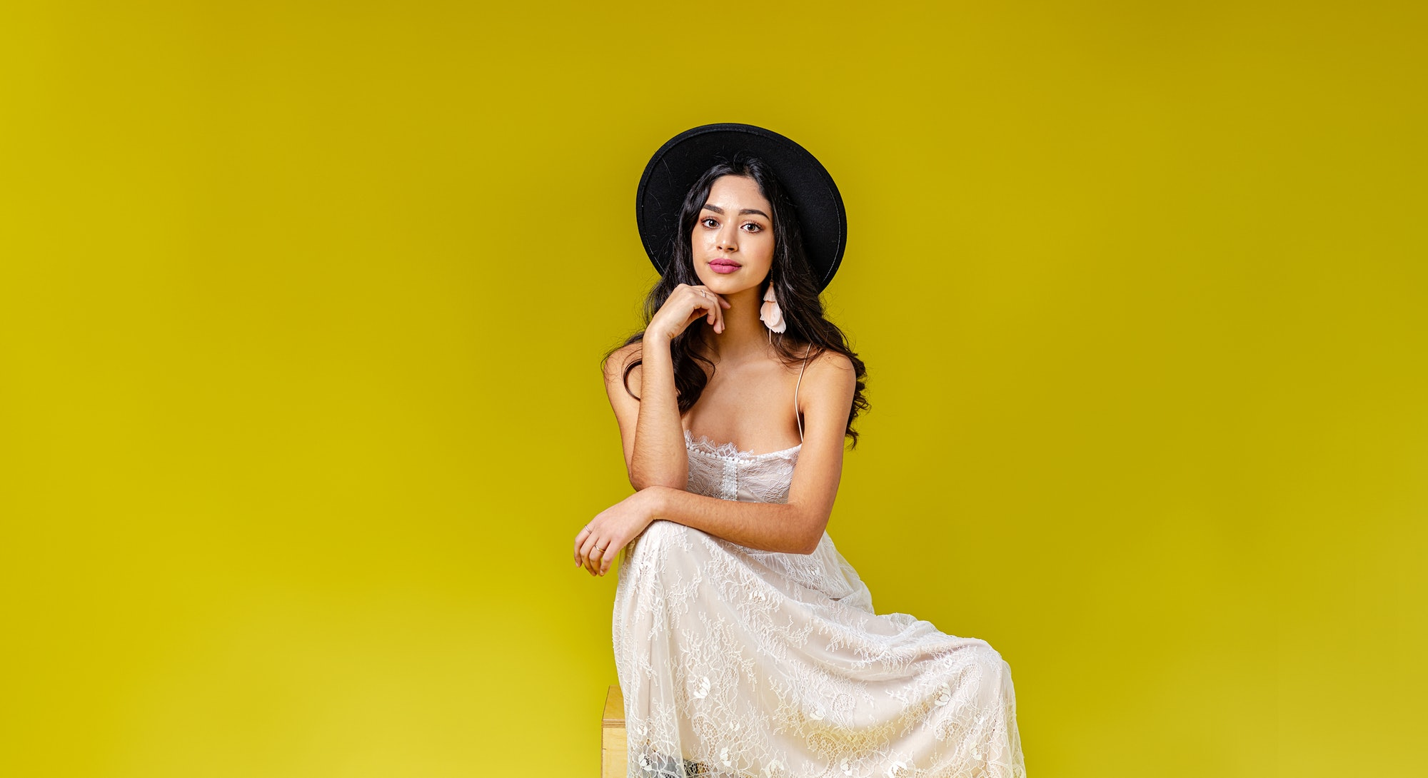 A portrait of attractive young woman wearing bohemian style dress and a black fedora hat, sitting in...