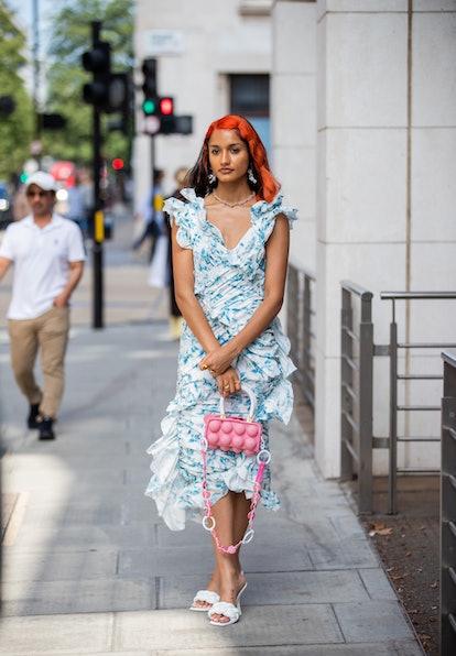LONDON, ENGLAND - SEPTEMBER 18: A guest is seen wearing blue dress, pink bag outside yuhan wang duri...