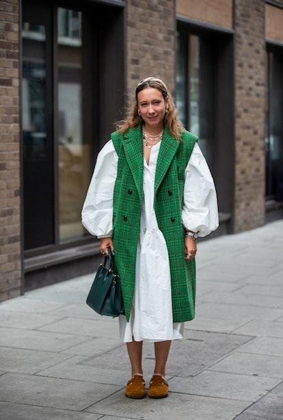 LONDON, ENGLAND - SEPTEMBER 19: A guest is seen wearing green sleeveless coat, white dress outside R...