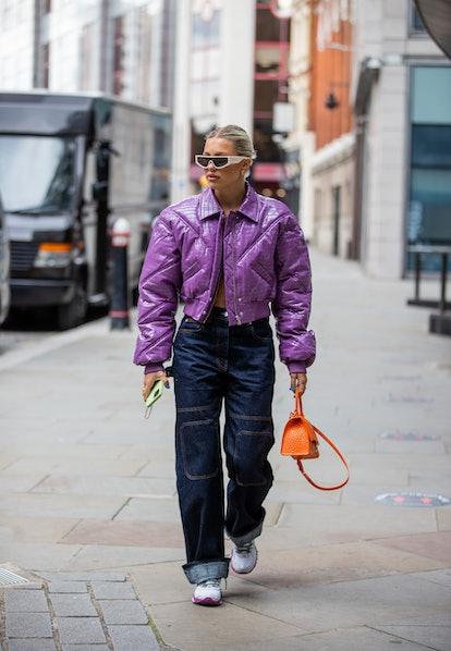LONDON, ENGLAND - SEPTEMBER 17: A guest is seen wearing purple cropped jacket, orange Balenciaga bag...