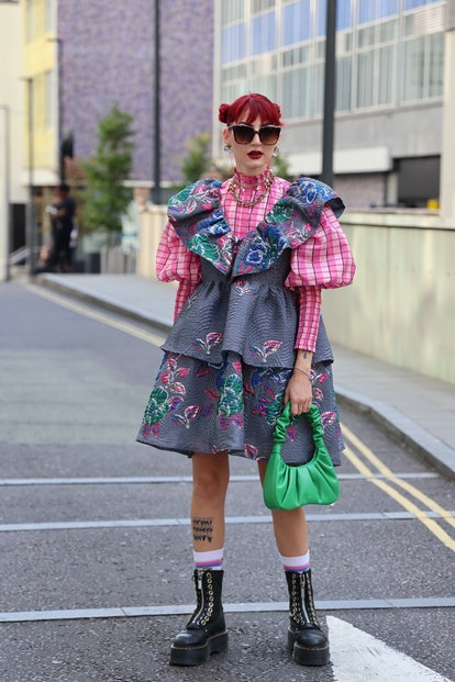LONDON, ENGLAND - SEPTEMBER 18: Guest wearing bright floral print dress and black boots, sunglasses,...