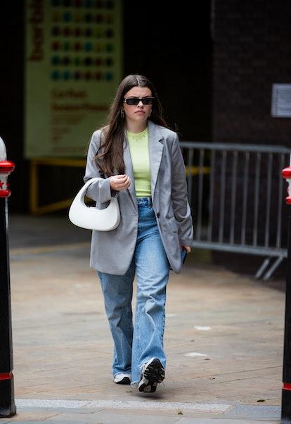 LONDON, ENGLAND - SEPTEMBER 17: A guest is seen wearing grey blazer, white bag, denim jeans outside ...