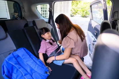 An Asian mother fastening her daughter safety seat belt in the car before send her to school.
