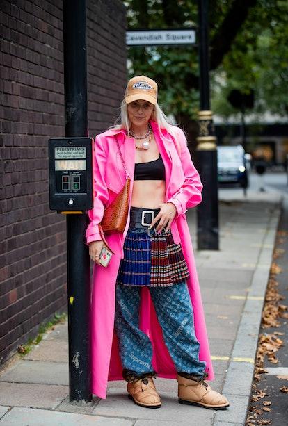 LONDON, ENGLAND - SEPTEMBER 18: A guest is seen wearing pink coat, skirt with belt, Louis Vuitton pa...