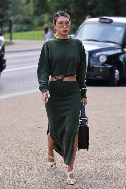 LONDON, ENGLAND - SEPTEMBER 20: Guest wearing green dress, black handbag, sunglasses attends ROKSAND...