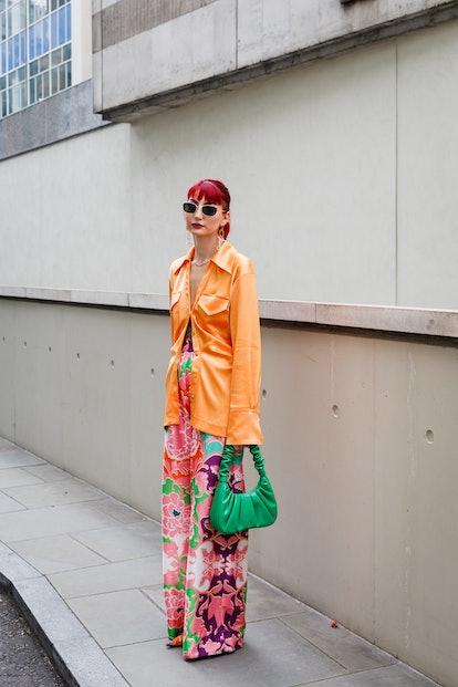 LONDON, ENGLAND - SEPTEMBER 19: A guest wearing an orange shirt, flower print trousers and a green b...