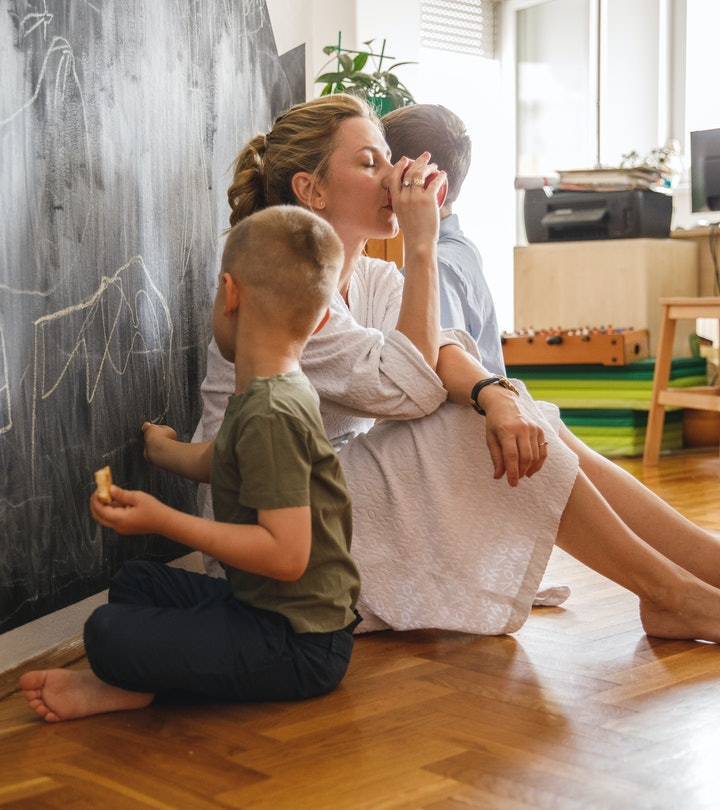 Full length shot of two little boys sitting on the floor and drawing with chalk on a blackboard wall...