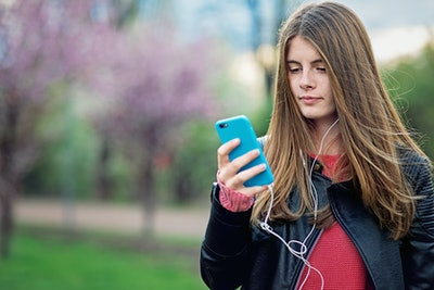 Portrait of beautiful teen girl listening to music in a park