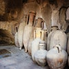 """Jugs lining the walls of a """"kitchen"""" are at the ruins of Herculaneum or Ercolano, Italy.  This Roman..."""