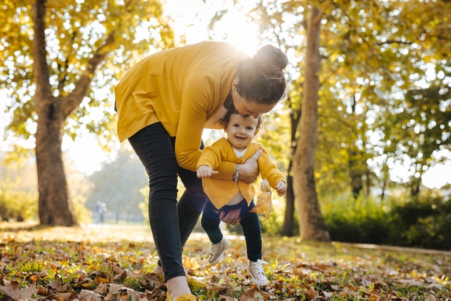 Mother is teaching her daughter to walk in sunny autumn park