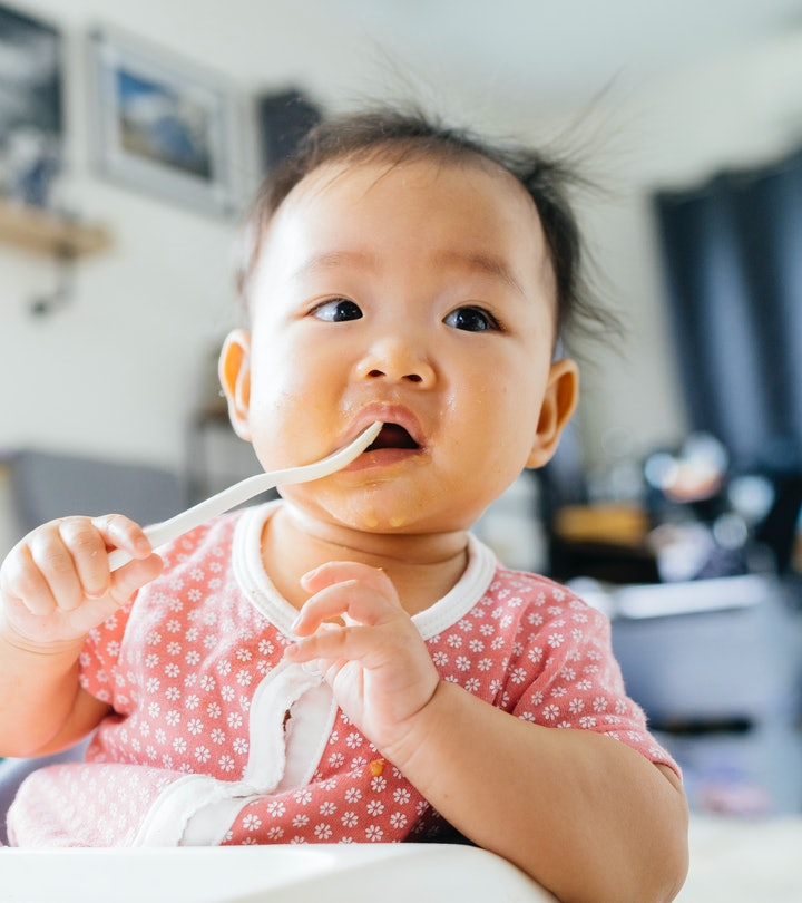baby girl holding spoon
