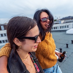 Two young latinx women drink on a rooftop. Here's what latinx means to them, and how they explain th...