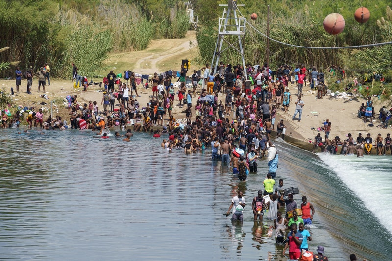 Migrants, many of them Haitian, cross the Rio Grande to get food and supplies near the Del Rio-Acuna...
