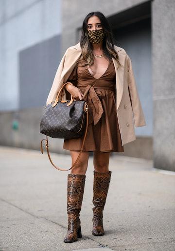NEW YORK, NEW YORK - SEPTEMBER 15: A guest is seen wearing a cream coat, brown dress and Louis Vuitt...