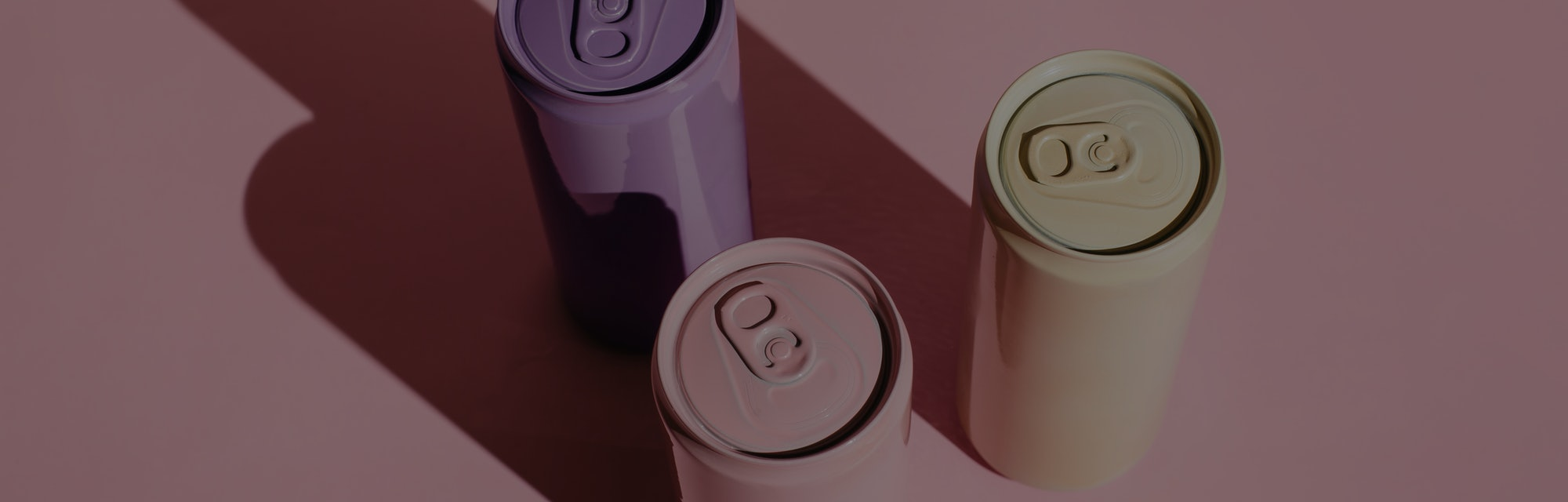 Pink, beige, lilac aluminum drink cans on pink background. Minimal creative still life. Zero waste, ...