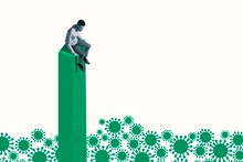 Scared young man sitting on top of green column while looking down at coronavirus against white back...