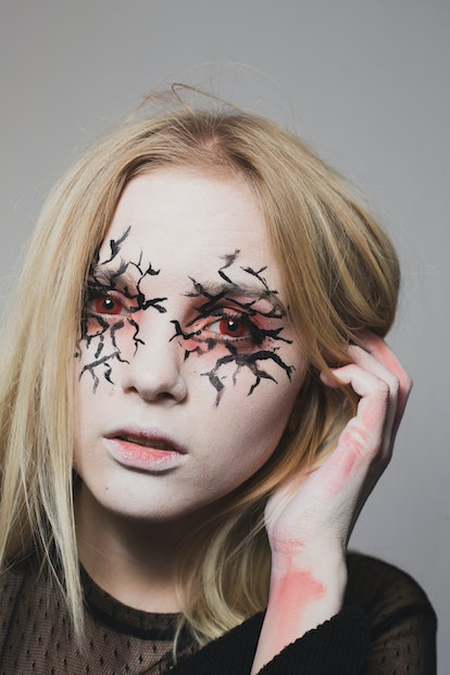 A young blonde woman with creepy, cracked Halloween eye makeup