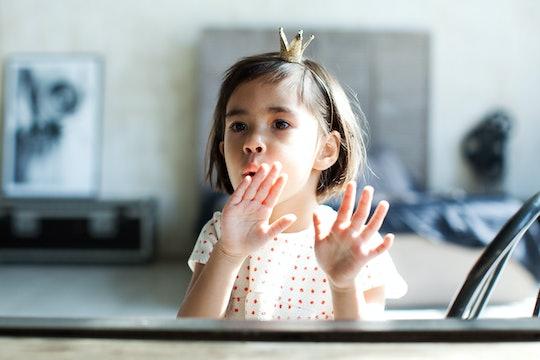 Little girl blowing on wet fingernails