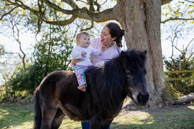 A baby girl sitting on a pony in a field while being supported by her mother who is standing next to...