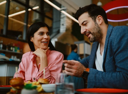 A moon in Virgo man and a woman on a dinner date, talking and eating.