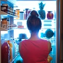 A young caucasian woman standing in front of the open refrigerator at late night, contemplating and ...