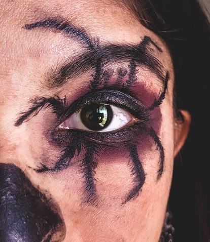 A young woman with a spider Halloween eye makeup look