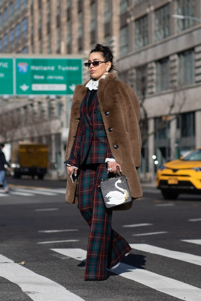 A guest is seen on the street wearing brown fur coat with navy/merlot/dark green plaid outfit on Feb...