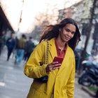 MILAN, ITALY - FEBRUARY 22: Model Jordan Daniels checks her phon and wears a yellow jacket after the...