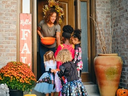 A diverse group of children, dressed in costumes, trick or treating in a residential USA neighborhoo...