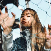 woman looking through fence with serious expression as she reflects on emotional meaning of october ...