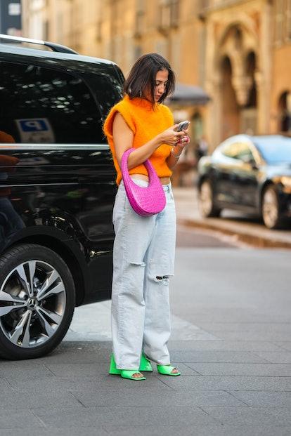 MILAN, ITALY - SEPTEMBER 22: A guest wears large earrings, an orange fluffy turtleneck / sleeveless ...